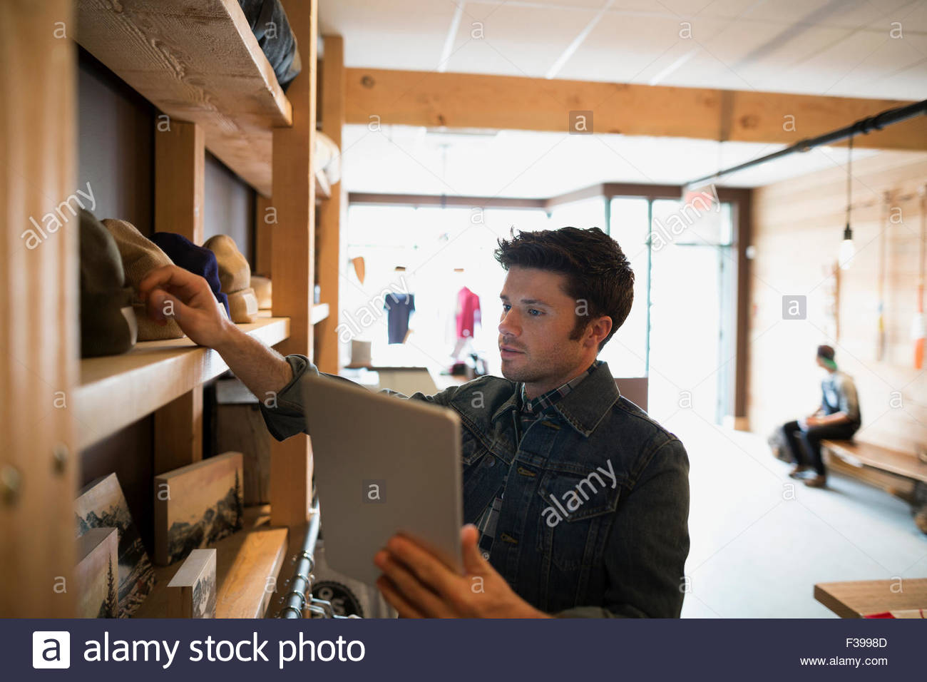 Worker with digital tablet in shop Photo Stock