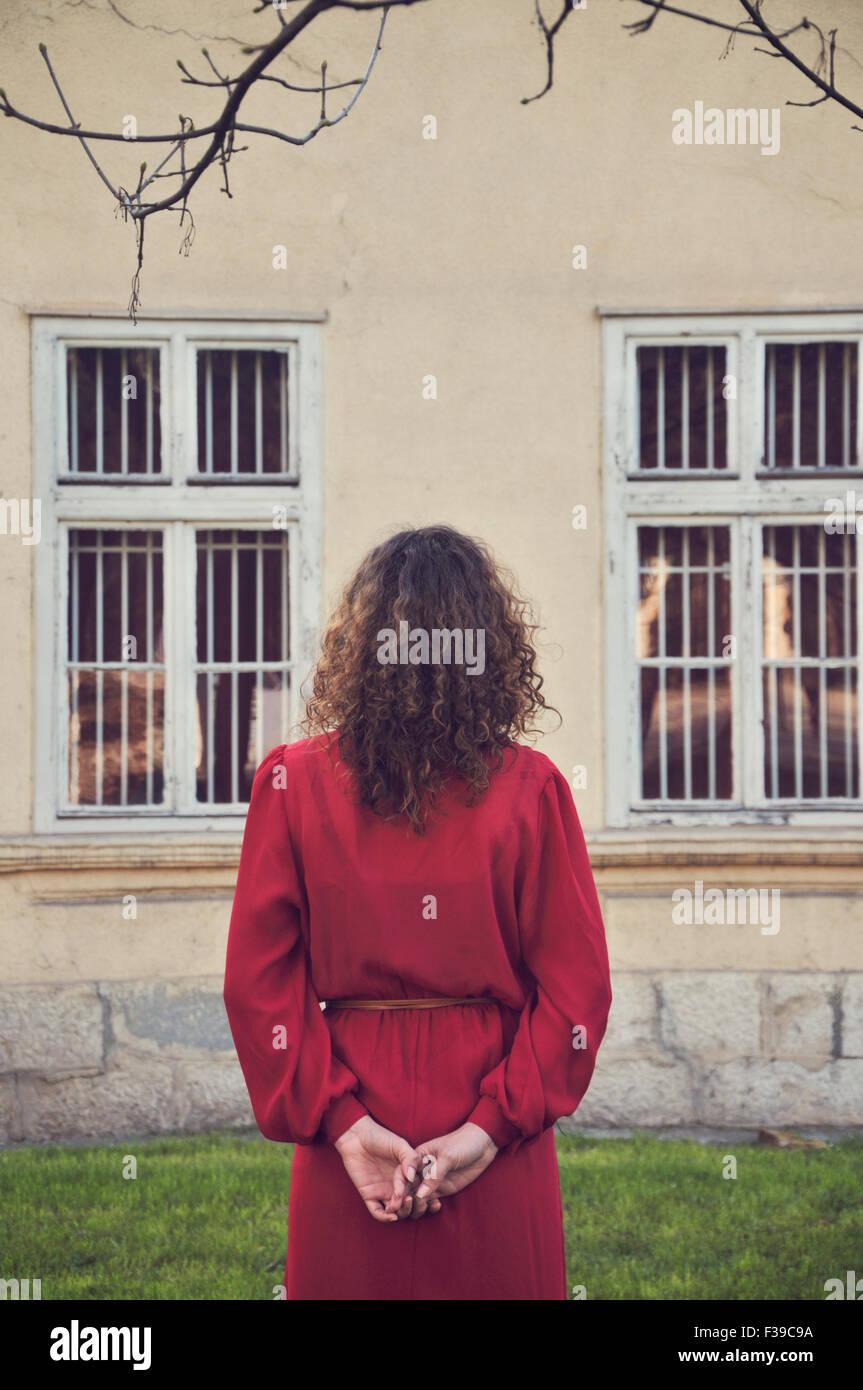 Femme en robe rouge debout à l'extérieur, vue arrière Photo Stock