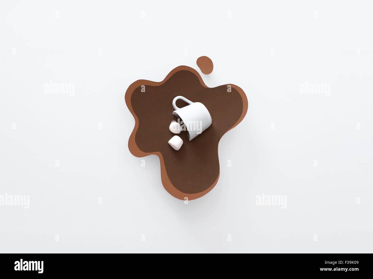 Mug conceptuel renversées, gisant dans une mare de papier fait du chocolat chaud avec des guimauves Photo Stock
