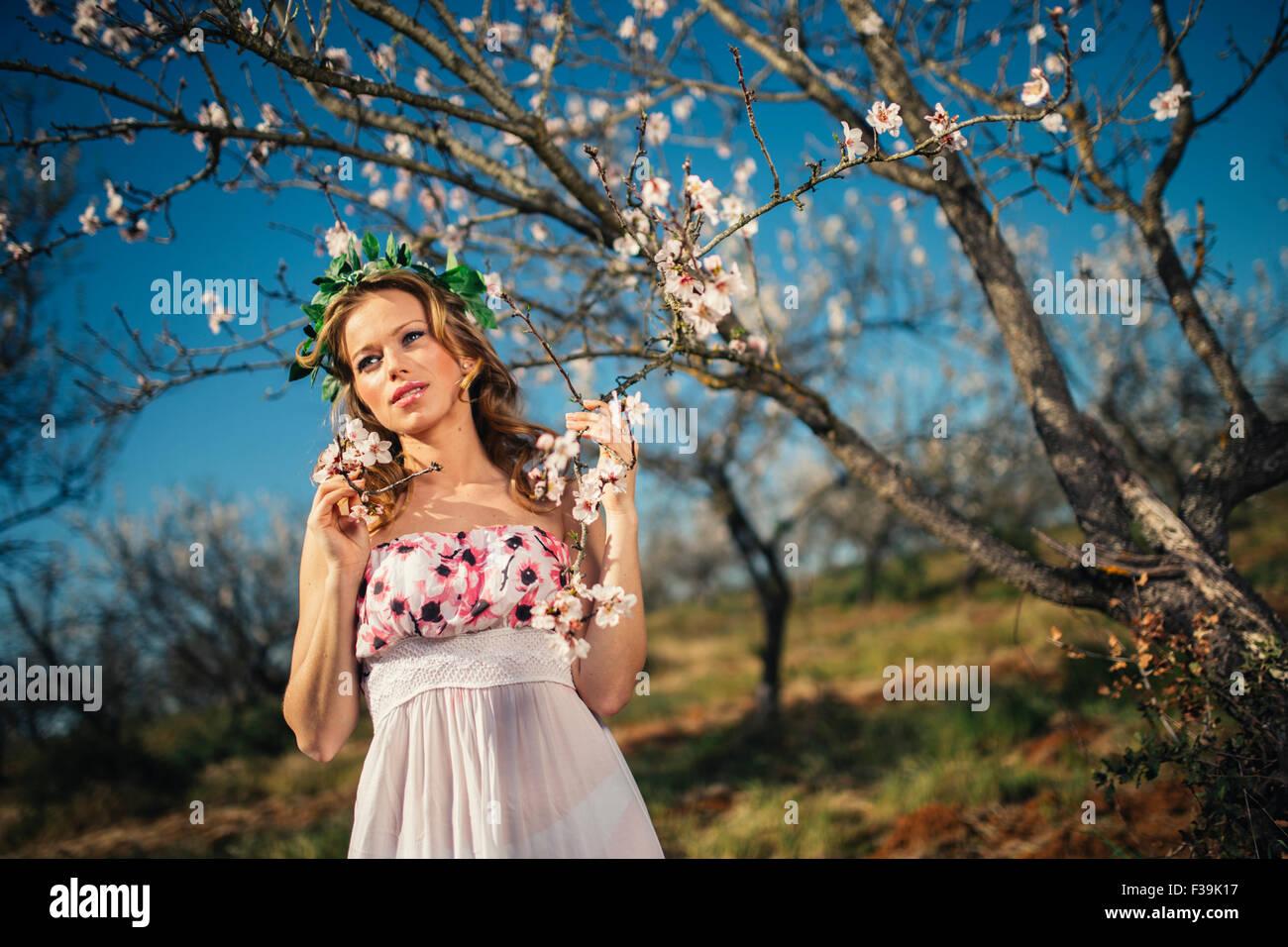 Portrait d'une femme portant une coiffe debout à côté d'un arbre en fleurs au printemps Photo Stock