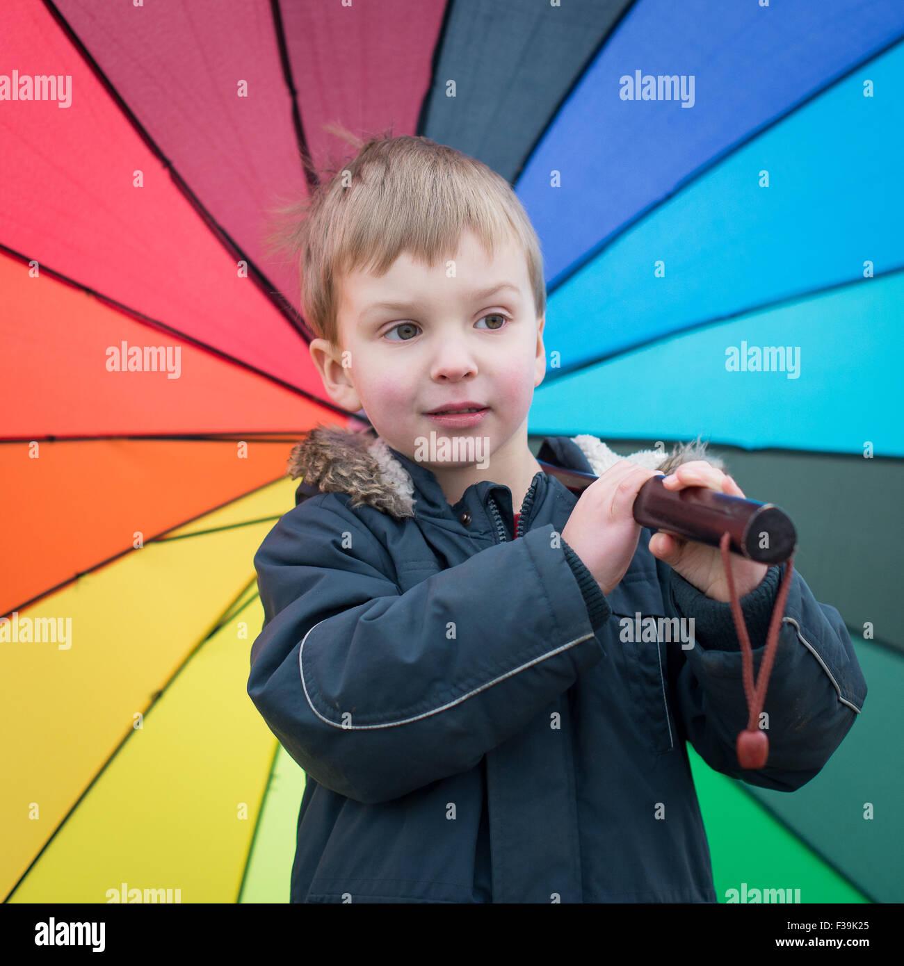 Boy carrying rainbow parapluie de couleur Photo Stock