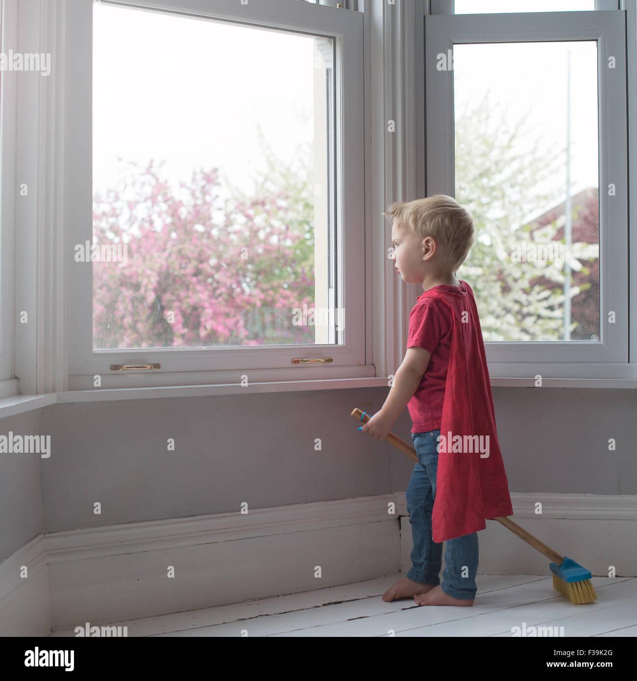 Garçon habillé comme super-héros, à la recherche d'une fenêtre Photo Stock