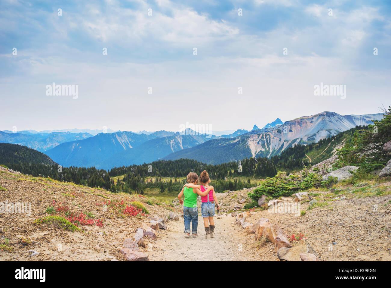Vue arrière du garçon et fille qui marche le long d'un chemin avec leurs bras autour de l'autre Photo Stock