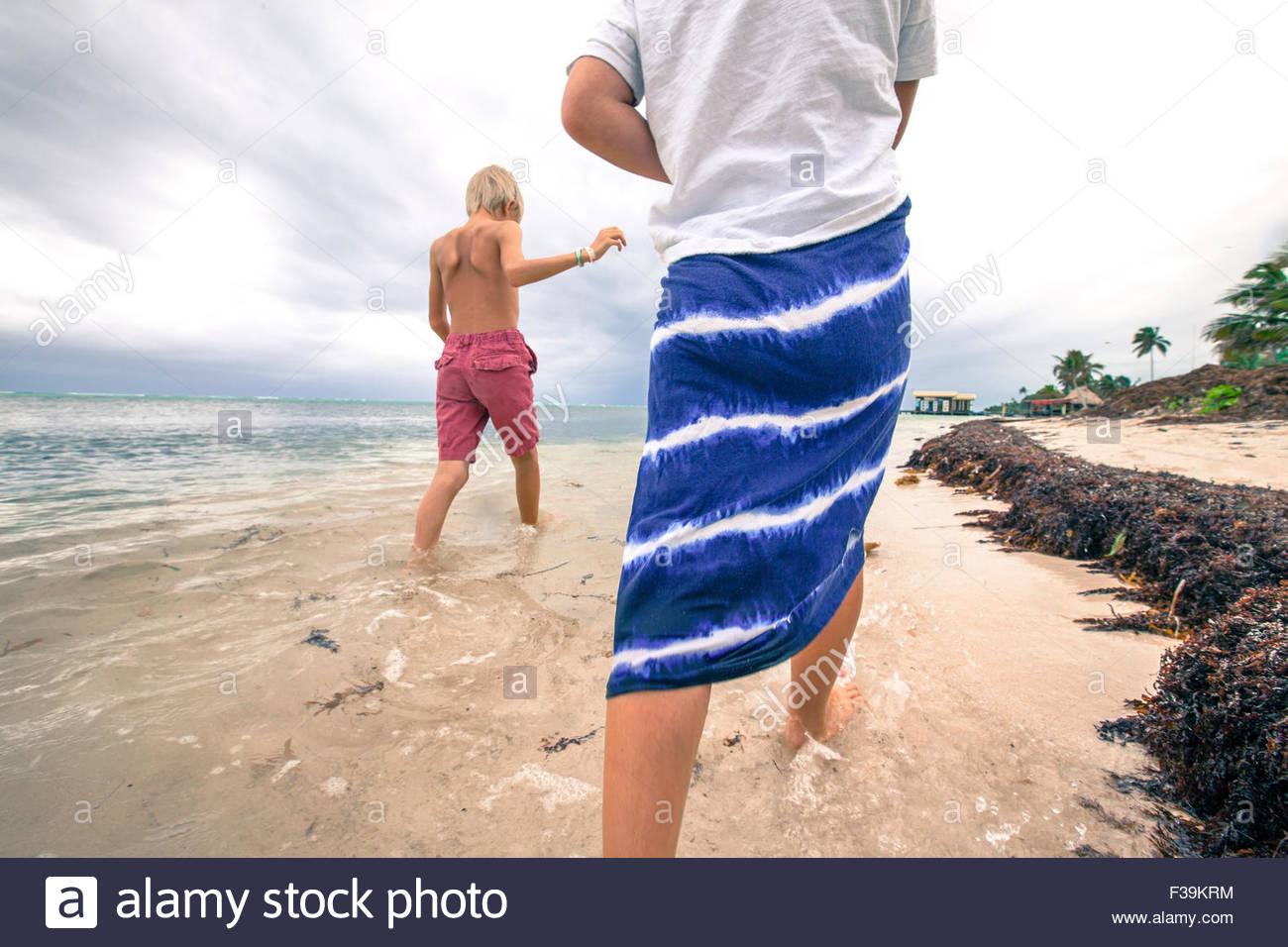 Deux enfants de marcher dans l'eau peu profonde à la plage, Belize Photo Stock