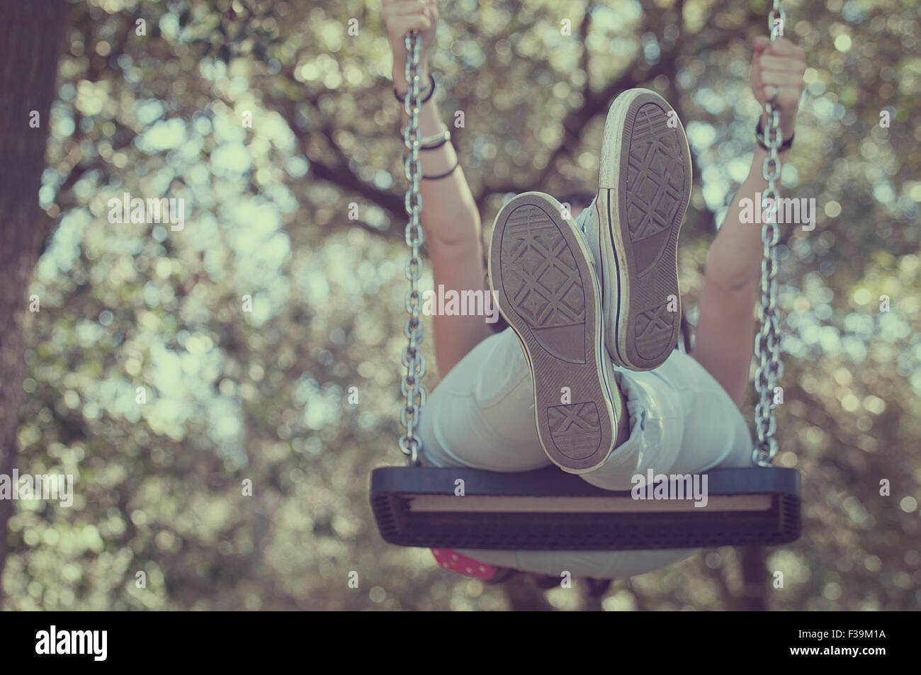 Low angle view of a young girl on a swing Photo Stock