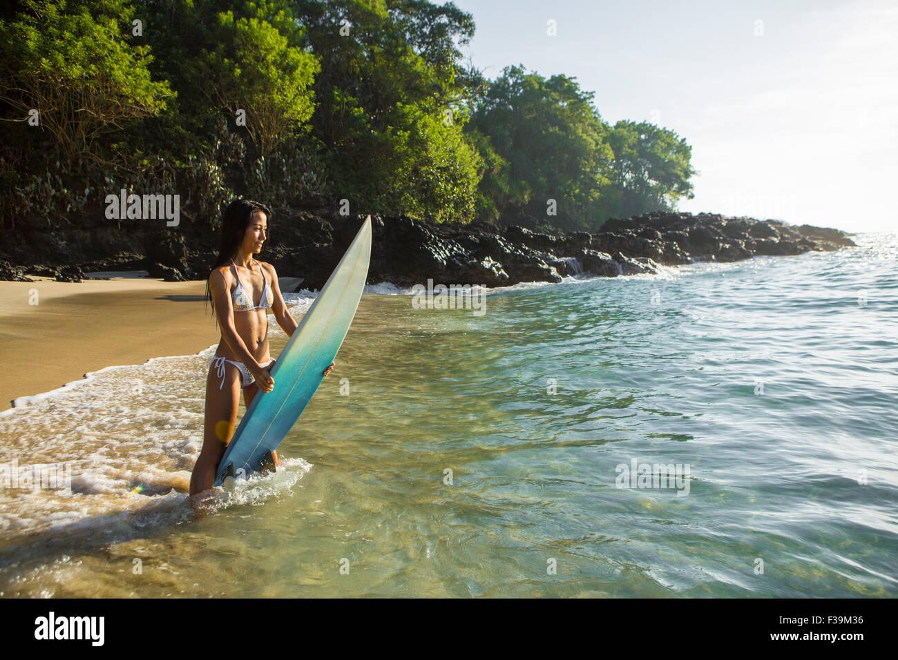 Mid adult woman sur la plage debout dans le surf tenant son conseil, Bali, Indonésie Photo Stock
