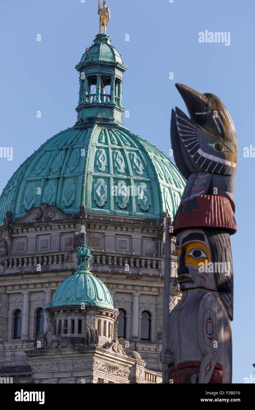 Totem en face de la coupole de l'édifice du Parlement de l'île de Vancouver, Victoria, British Columbia Canada Banque D'Images