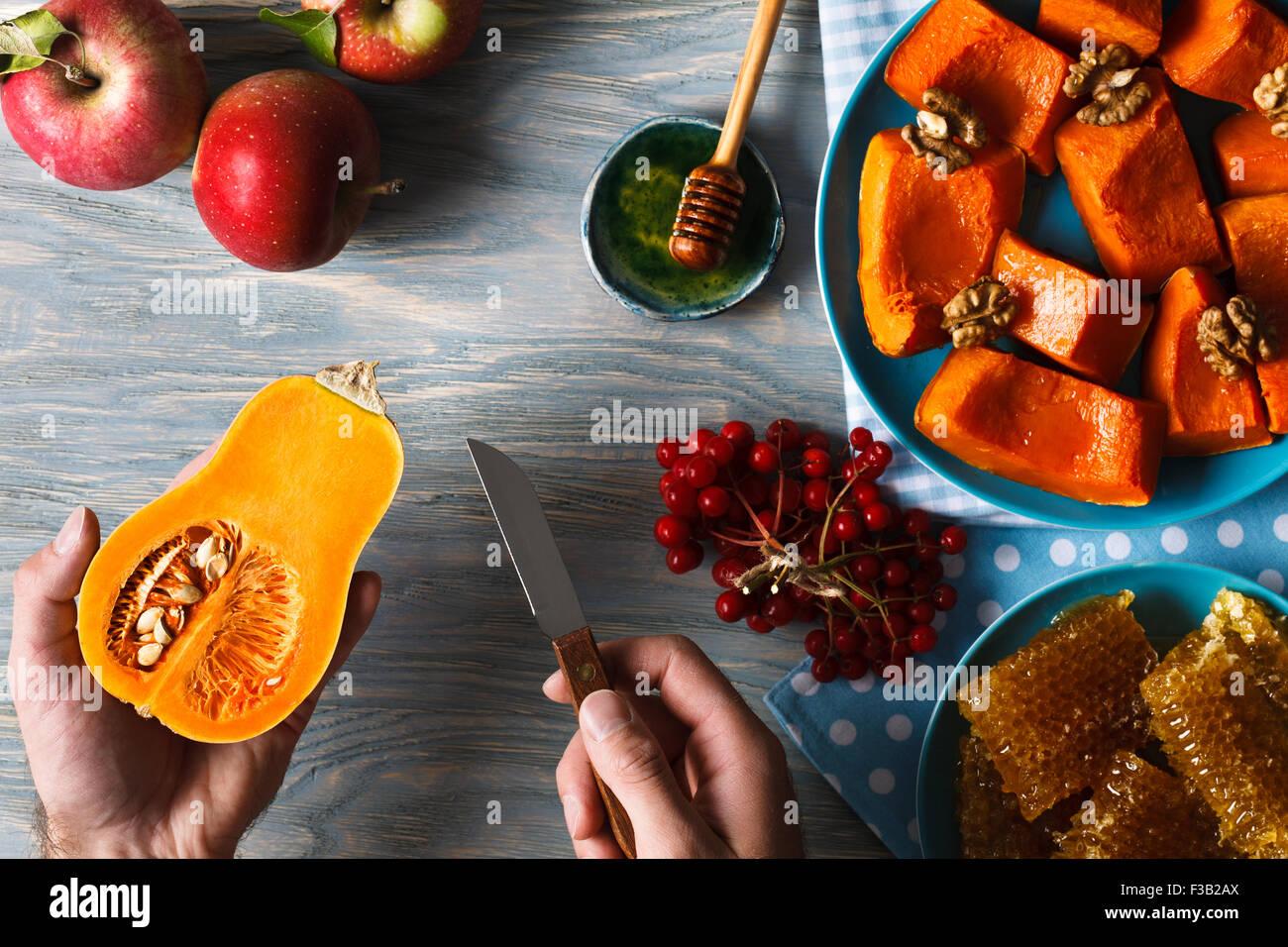 Menu d'automne. Homme mains tenant peu citrouille et un couteau dans le contexte des pommes fraîches, un tas de petits fruits viburnum, h Banque D'Images