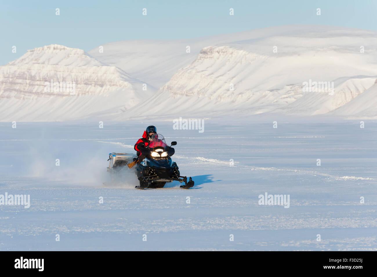 La motoneige en Tempelfjorden sur la glace de mer avec ses montagnes couvertes de neige, Spitsbergen, Svalbard, Norvège. Banque D'Images