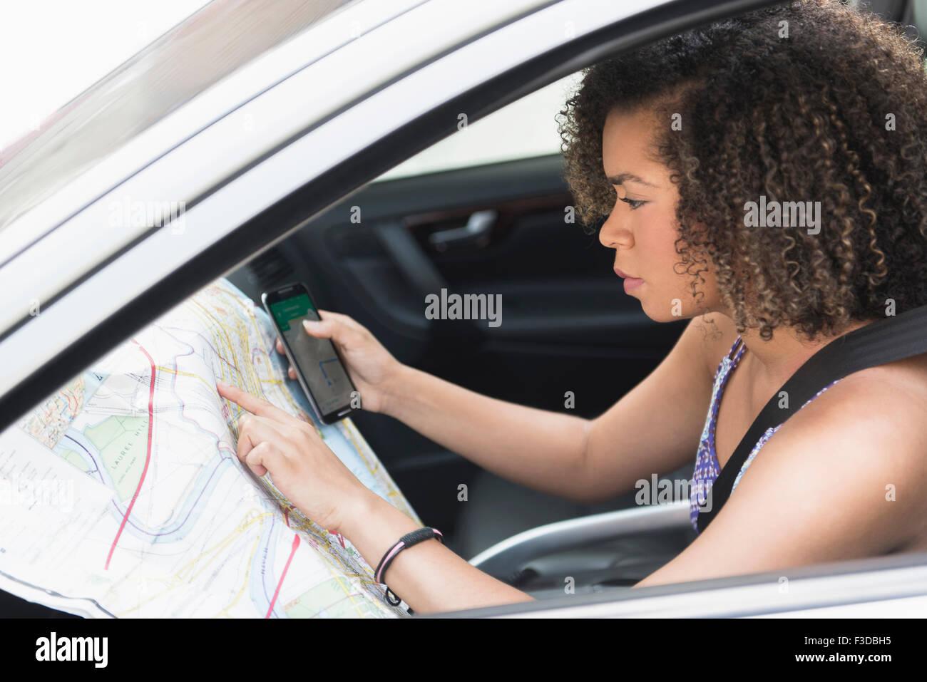 Jeune femme contrôle map in car Photo Stock