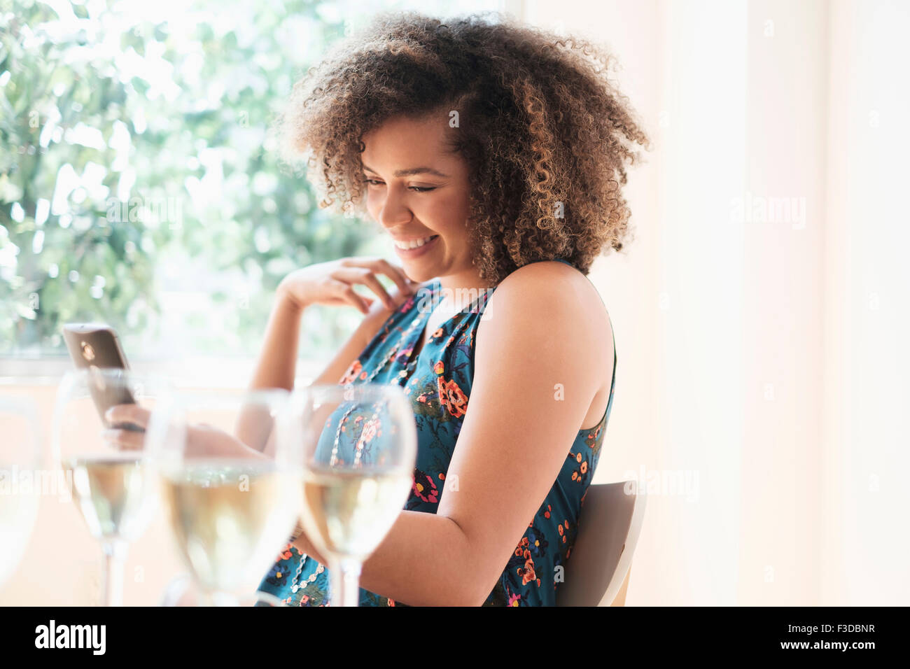 Young woman using smart phone at restaurant Banque D'Images