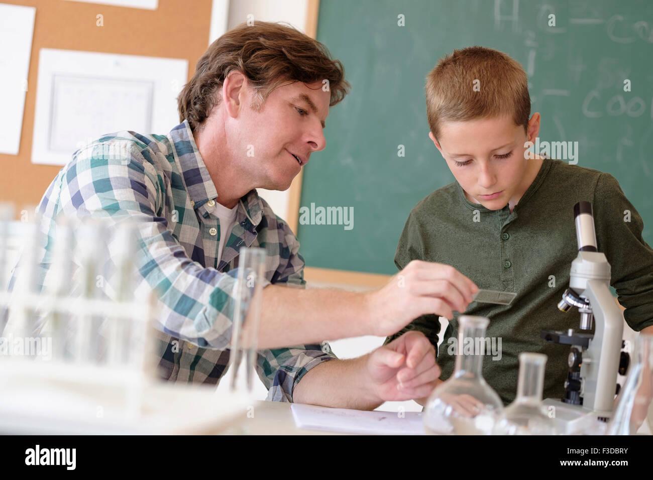 Parler avec l'enseignant étudiant (8-9) in classroom Photo Stock