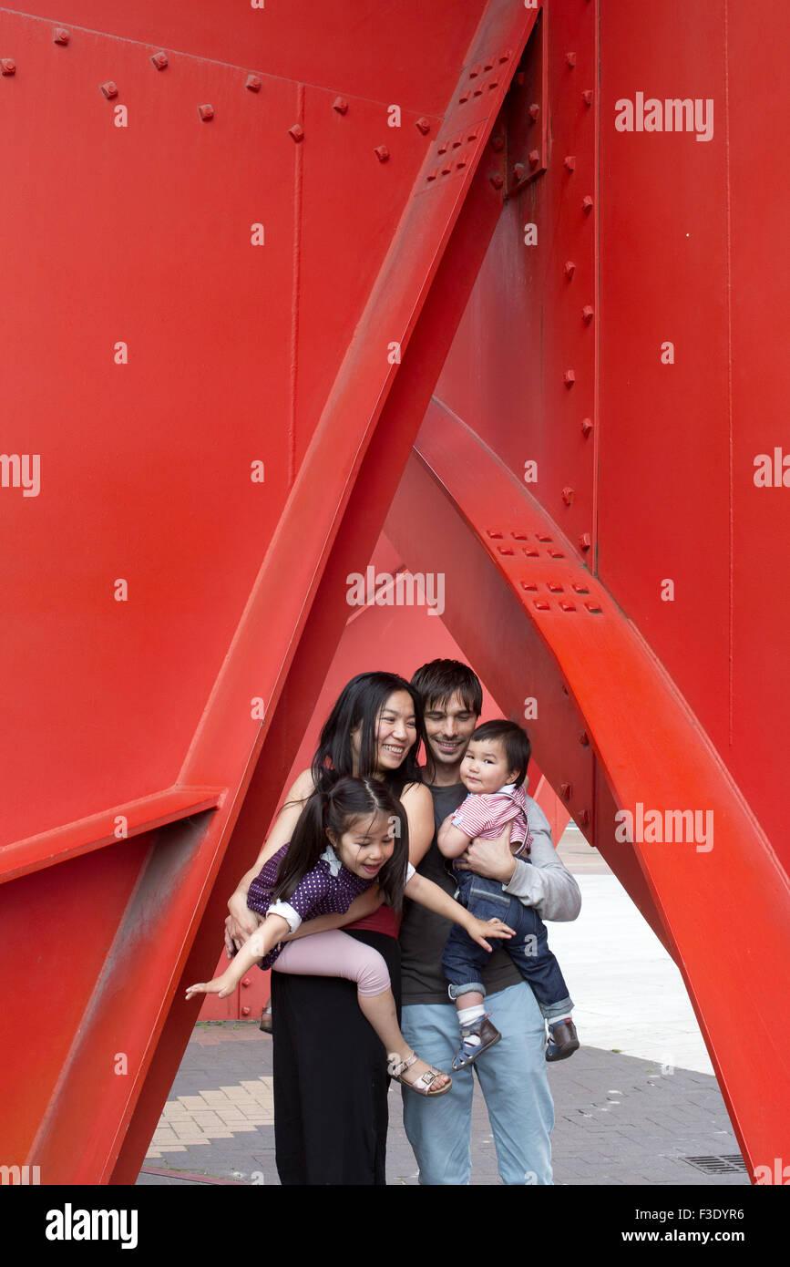 Famille avec deux enfants se tenant sous la sculpture Photo Stock