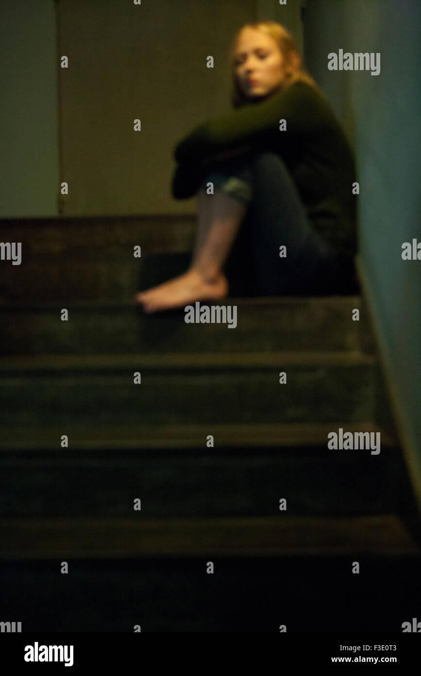 Femme assise seule dans l'escalier Photo Stock