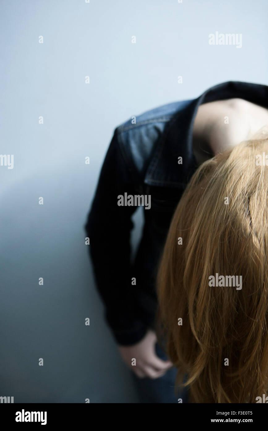 Femme menant de l'avant en laissant de longs cheveux blonds pendre Photo Stock
