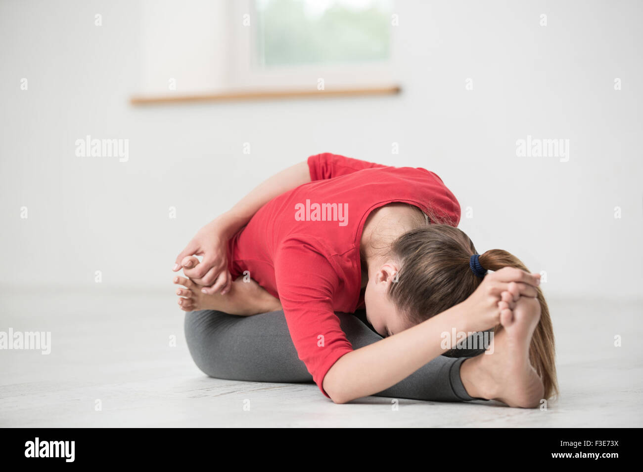 Portrait of a young woman doing stretching exercises in gym Photo Stock
