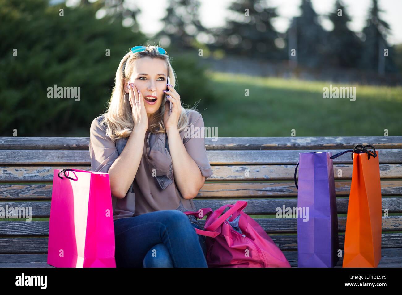 Jeune femme européenne à l'aide d'un téléphone sur un banc après le shopping. Stupéfait Photo Stock