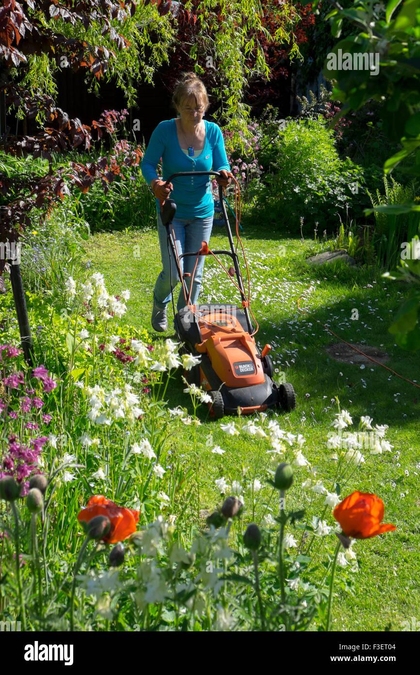 Femme âgée la pelouse avec une tondeuse électrique, Pays de Galles, Royaume-Uni Photo Stock