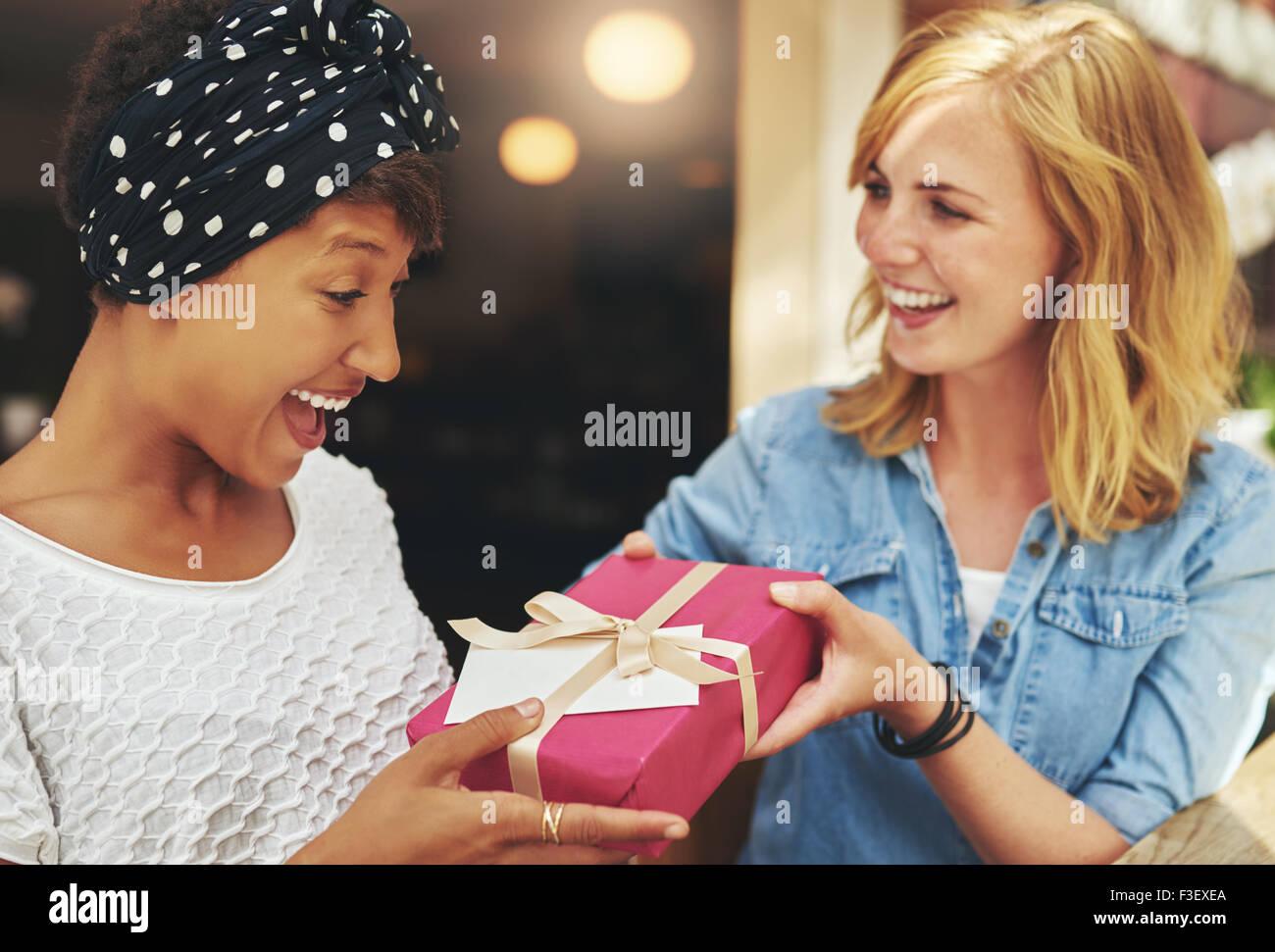 Jolie jeune femme blonde donnant un beau young African American friend un cadeau surprise cadeau avec du papier Photo Stock