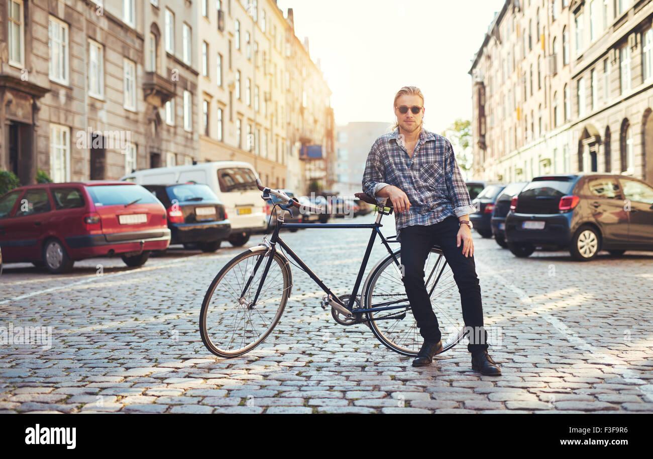 La vie dans la ville, portrait de jeune homme assis sur son vélo Photo Stock