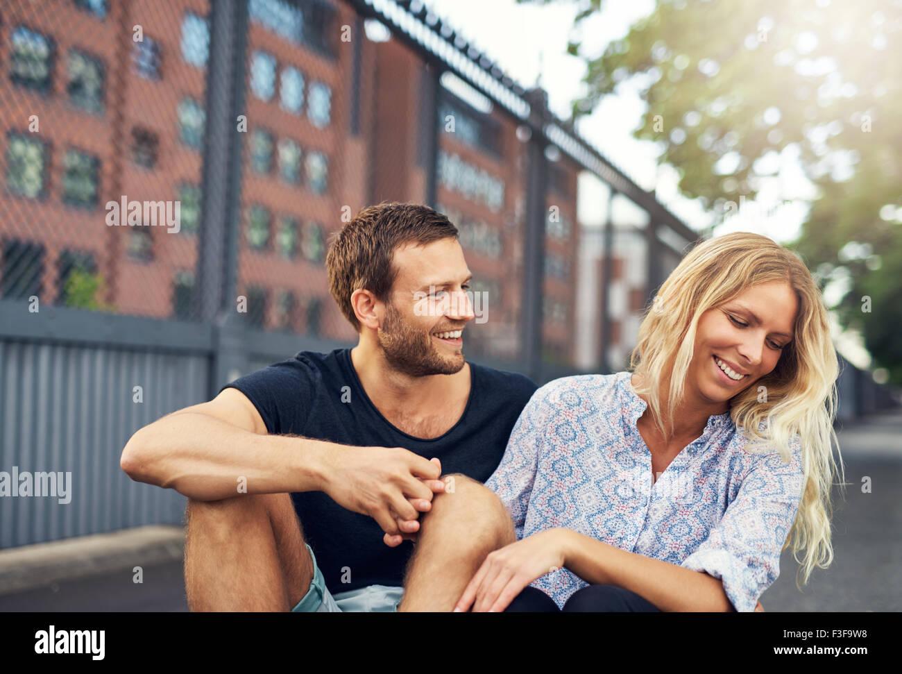 Taquiner l'homme à sa petite amie, grande ville couple in a park Banque D'Images