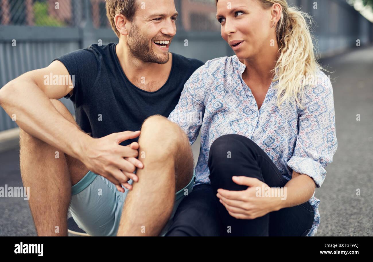 Couple ayant un bon moment tout en restant assis sur le sol Photo Stock