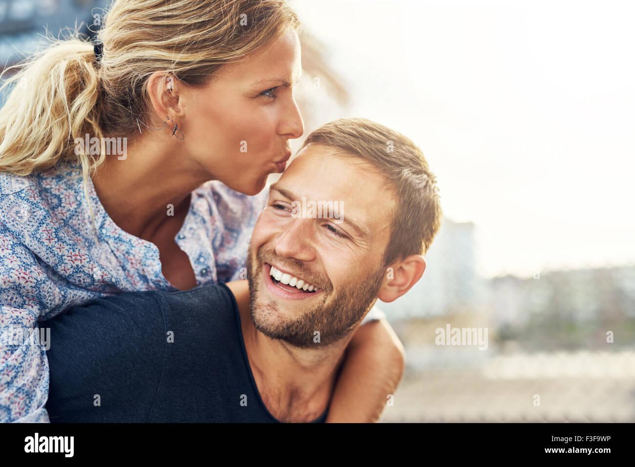 Woman Kissing Man alors qu'il rit, jeune couple Photo Stock