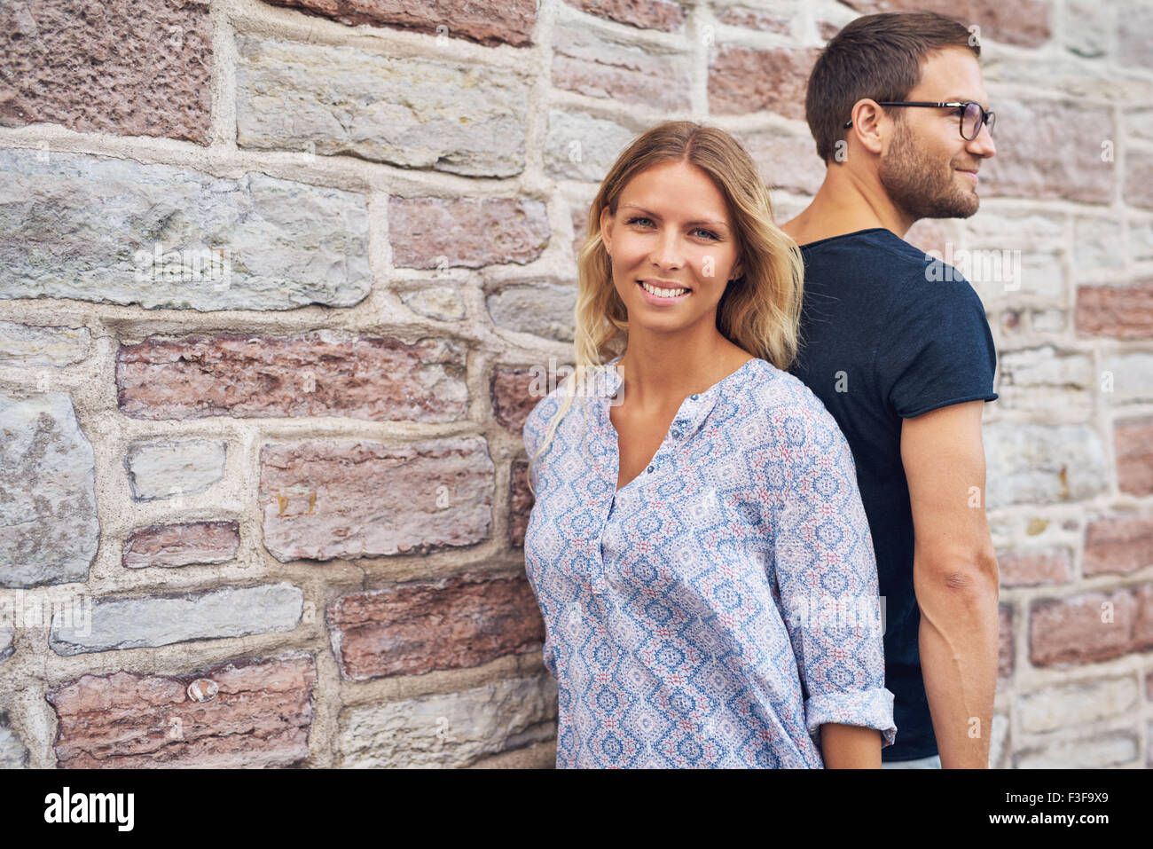 Couple debout dos contre l'autre contre un mur Photo Stock