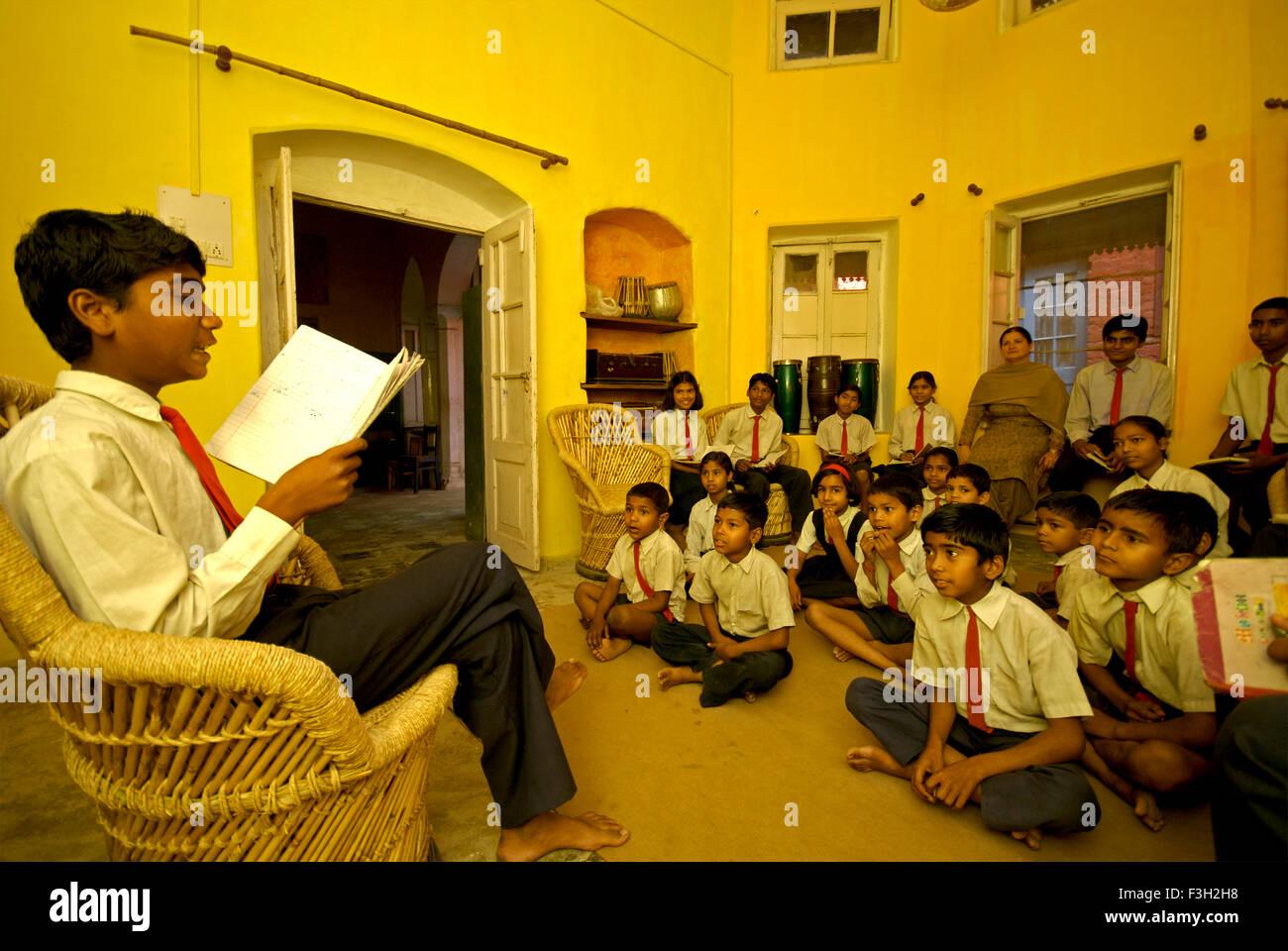 Boy reading essai de camarades de classe dans la salle de musique de Nanhi Dunya; école; l'Uttaranchal Photo Stock