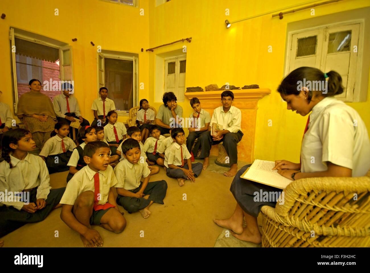 Girl reading essai de camarades de classe dans la salle de musique de Nanhi Dunya; école; l'Uttaranchal Photo Stock