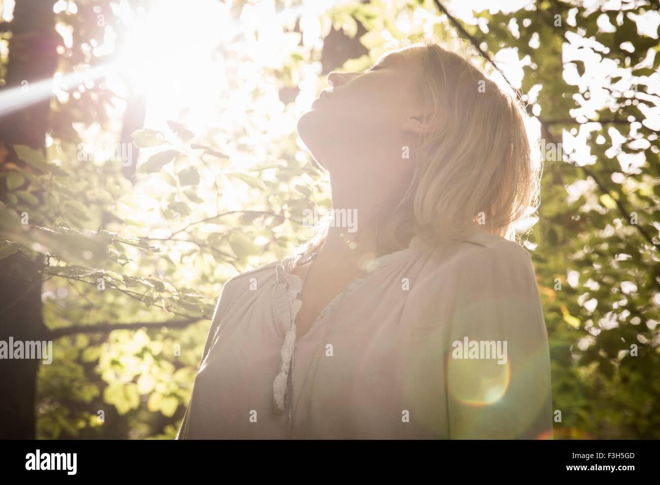Mature Woman standing dans le flux de lumière en forêt Photo Stock