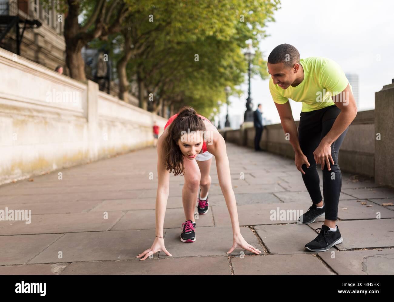 Formateur de jeunes hommes pratiquant commence avec female runner on riverbank Photo Stock