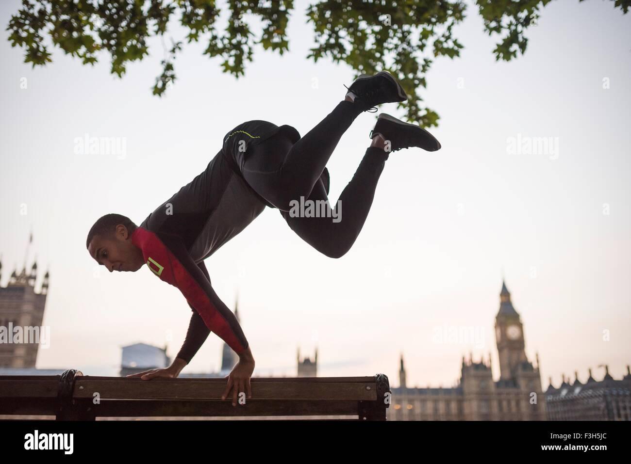 Jeune homme saute au-dessus de banc de parc sur Southbank, Londres, UK Photo Stock