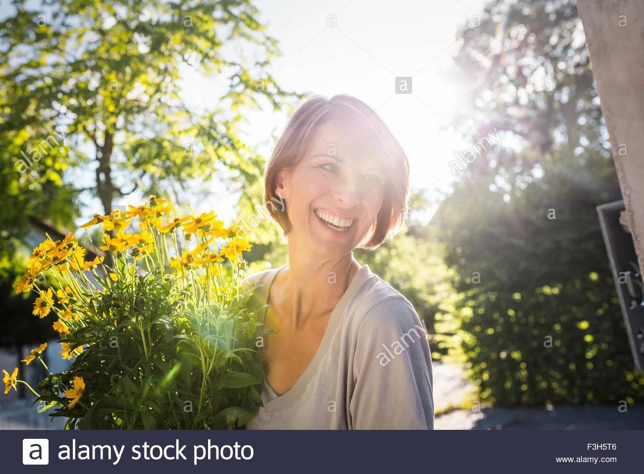 Femme mature avec des fleurs jaunes pot pour nouvelle maison Photo Stock