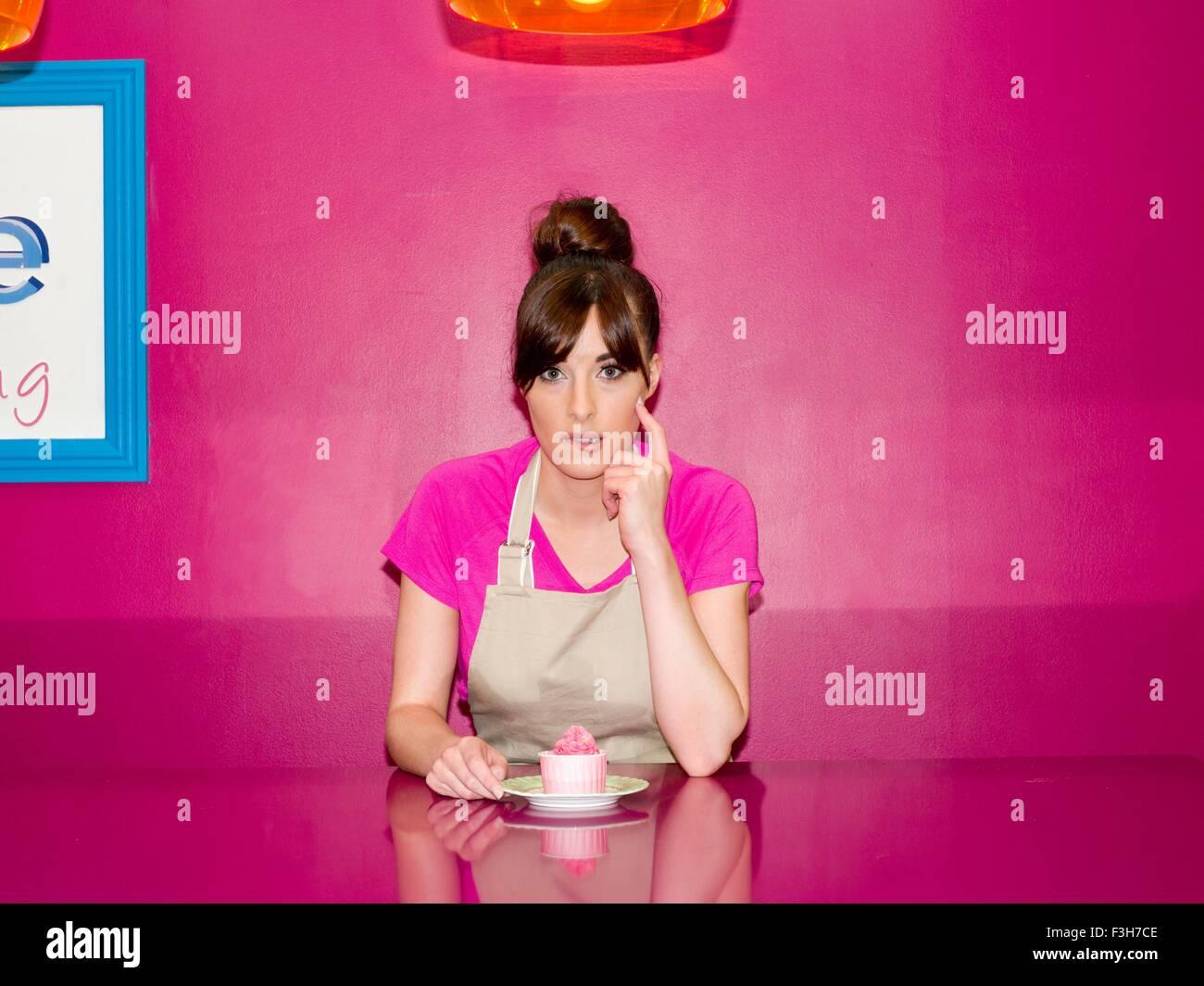 Jeune femme, qui travaillait dans une pâtisserie, assis avec cupcake en face d'elle Photo Stock