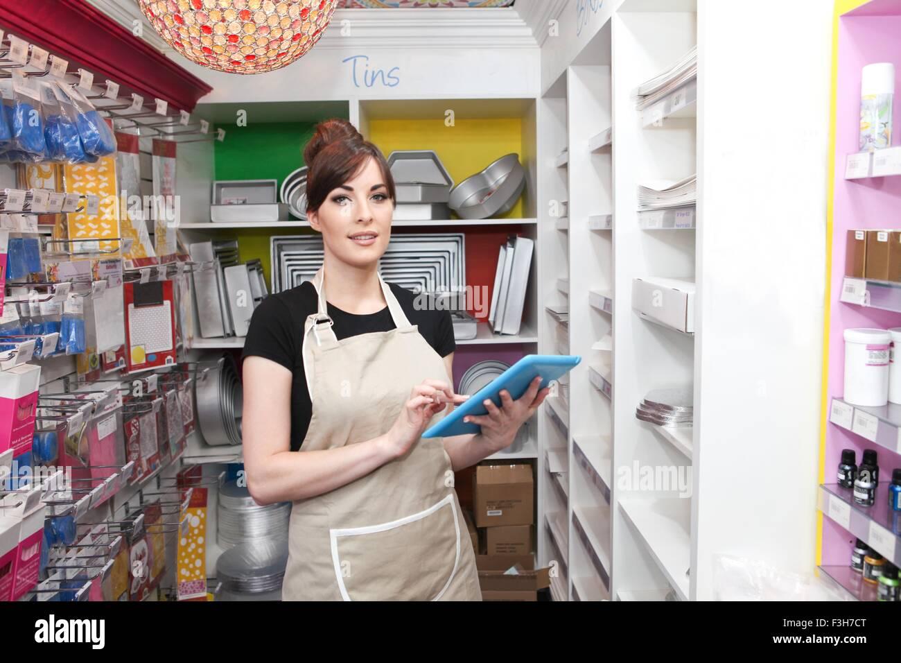 Jeune femme travaillant dans une pâtisserie, holding digital tablet, comptage stock Photo Stock