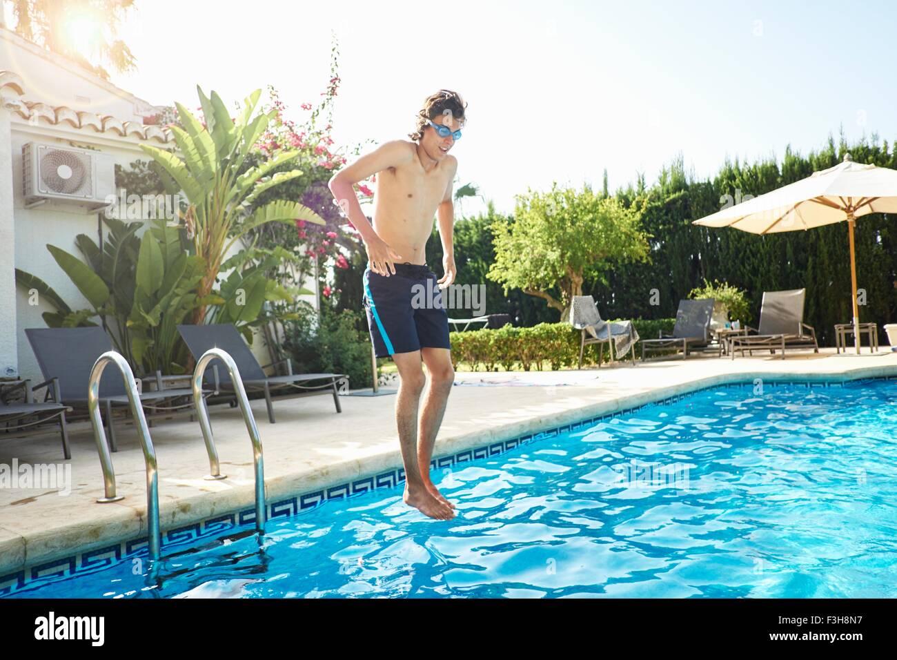 Jeune homme portant des lunettes de natation jumping into swimming pool Photo Stock