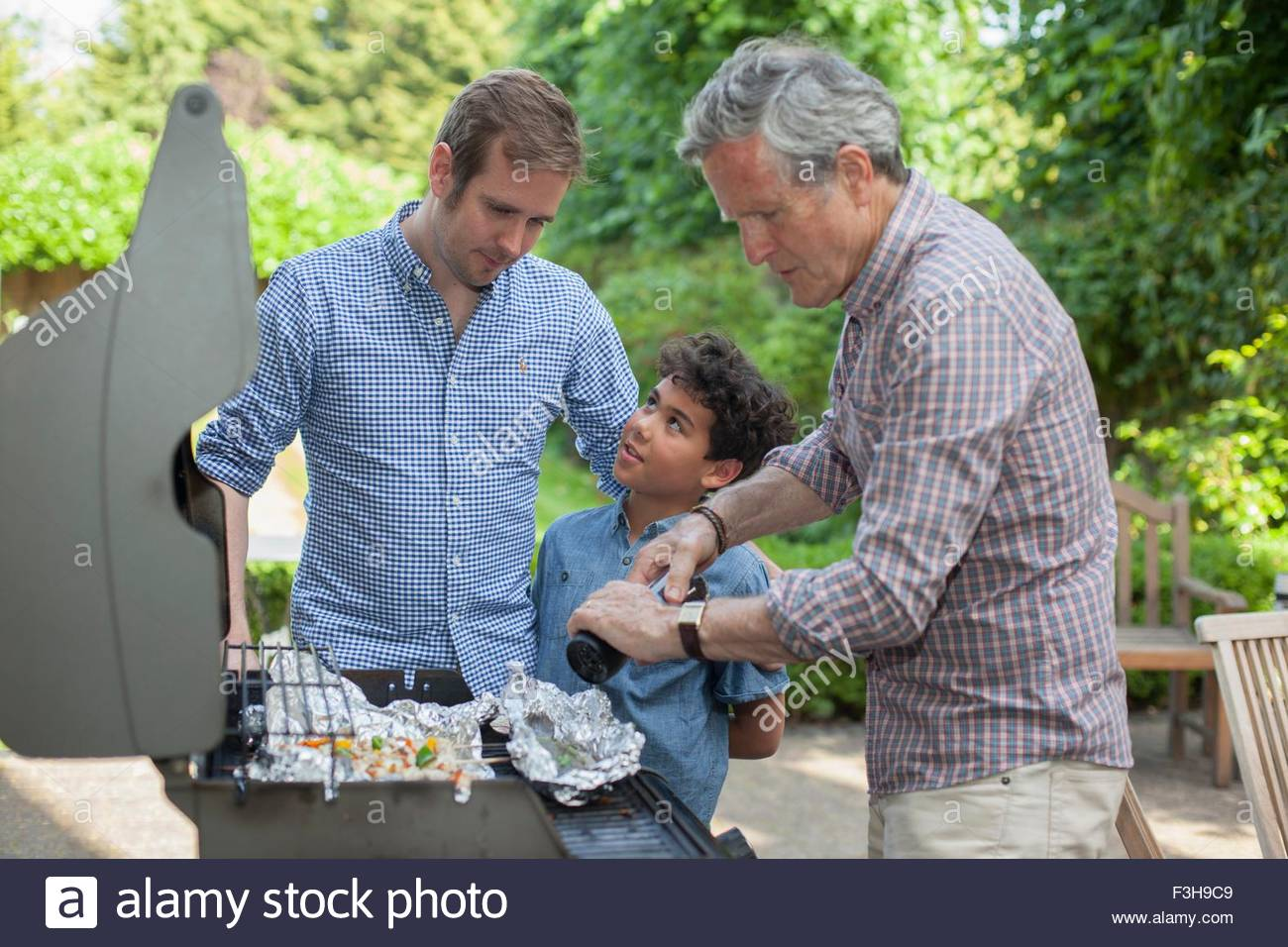 Family la cuisson sur barbecue Photo Stock