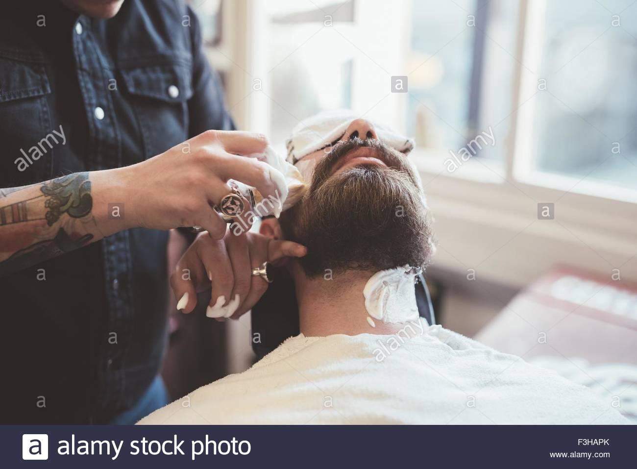 Coiffure L'application de la crème à raser clients doivent faire face dans un salon de coiffure Photo Stock