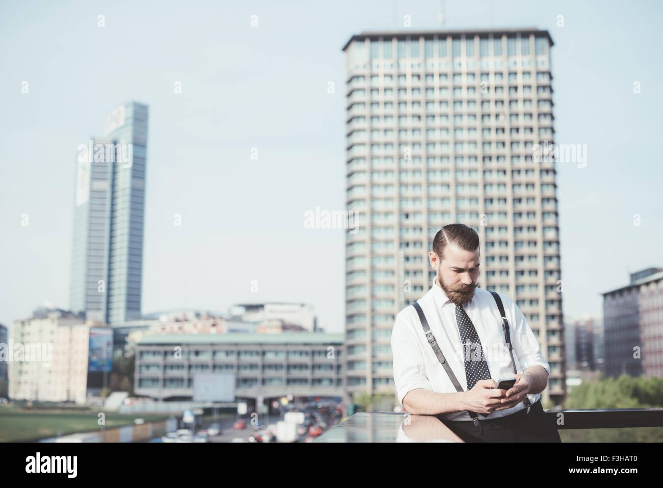 Homme élégant smartphone lecture mise à jour du texte sur balcon bureau Photo Stock