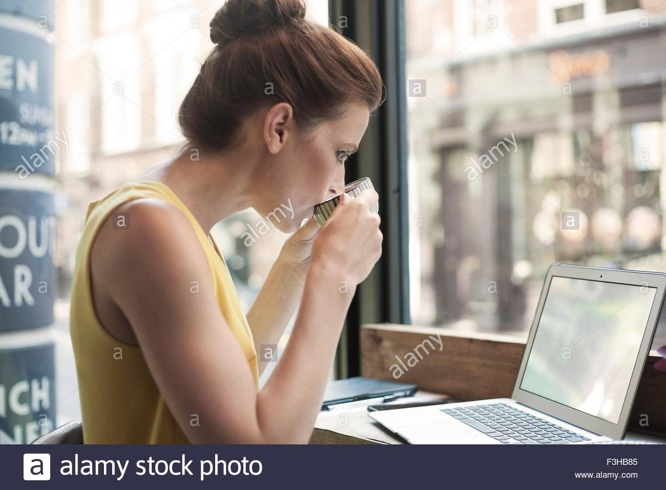 Une jeune brunette woman sitting in a cafe travailler Photo Stock