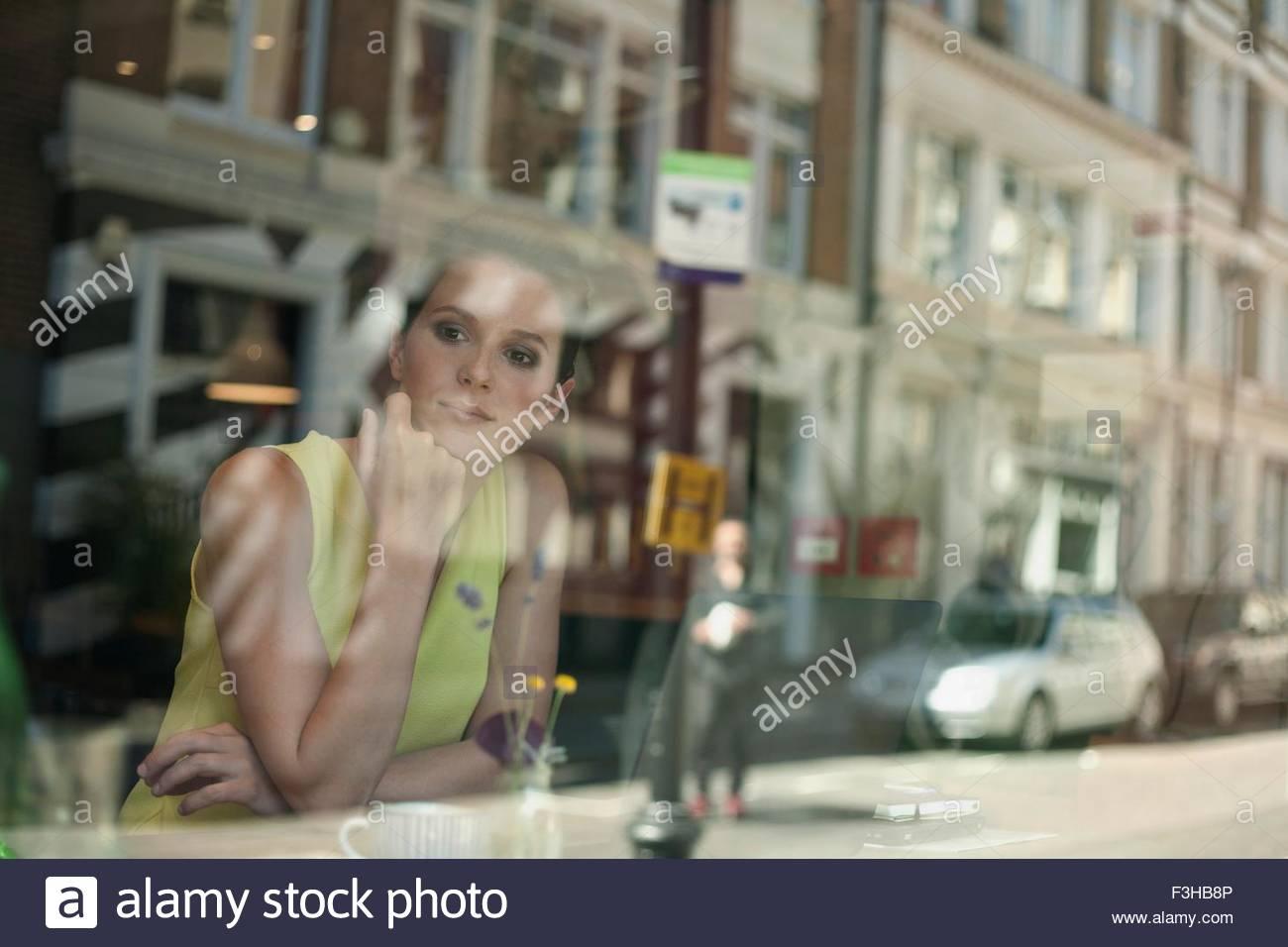 Une jeune femme brune assise dans un café en regardant par la fenêtre Photo Stock