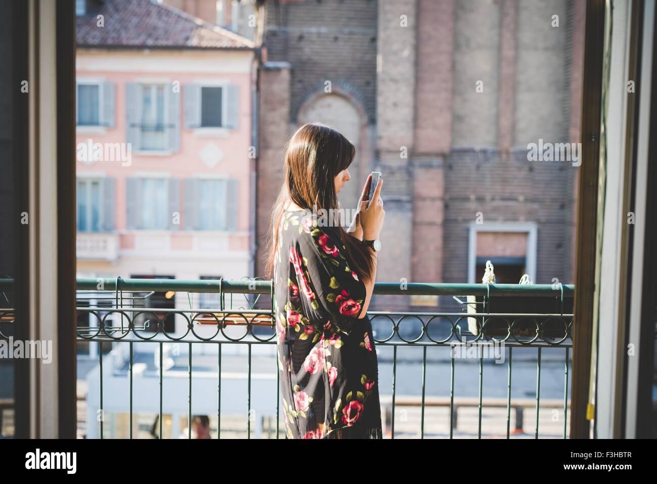 Jeune femme lisant des textes sur smartphone balcon ville Photo Stock
