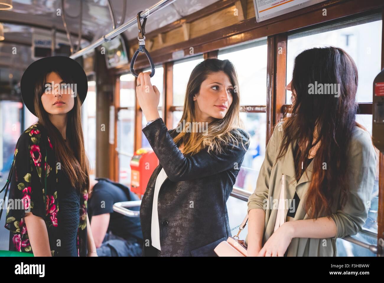 Trois jeunes femmes qui voyagent sur le tram de la ville Photo Stock