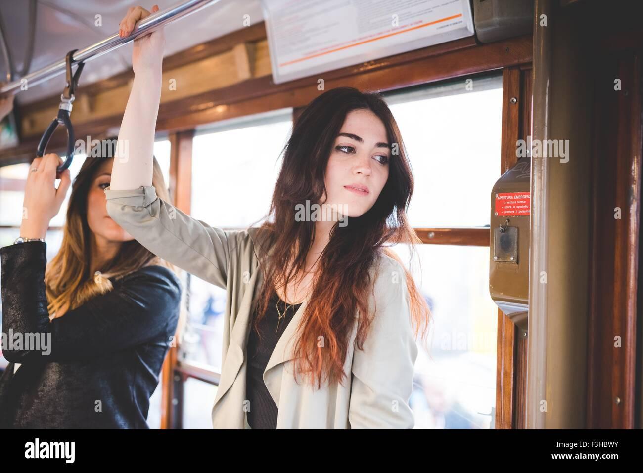 Deux jeunes femmes voyageant sur le tram de la ville Photo Stock