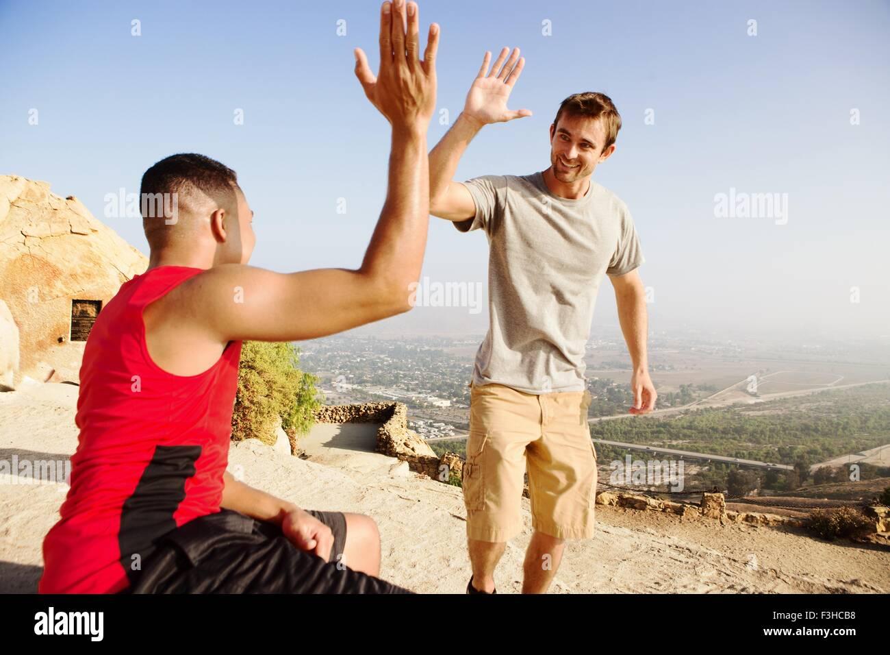 Deux amis masculins, en haut de la montagne, offrant un rapport cinq Photo Stock