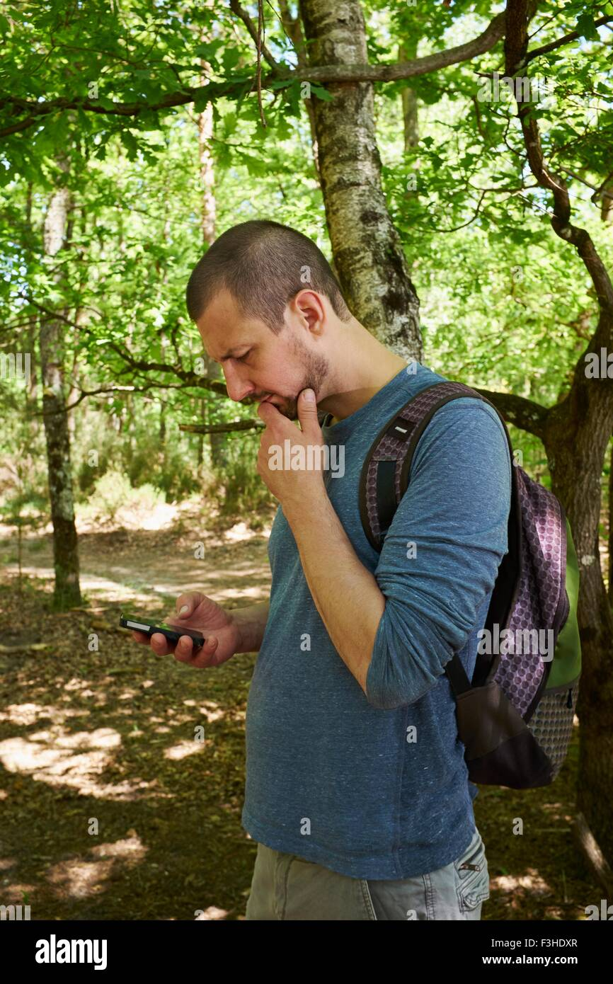 Male hiker looking down at smartphone in forest Photo Stock