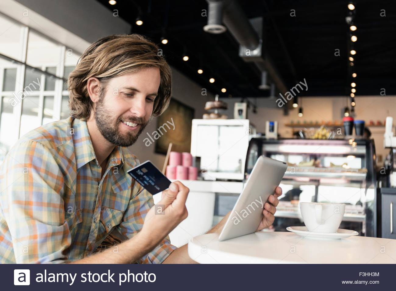 Mid adult man in coffee shop, using digital tablet, holding credit card Photo Stock