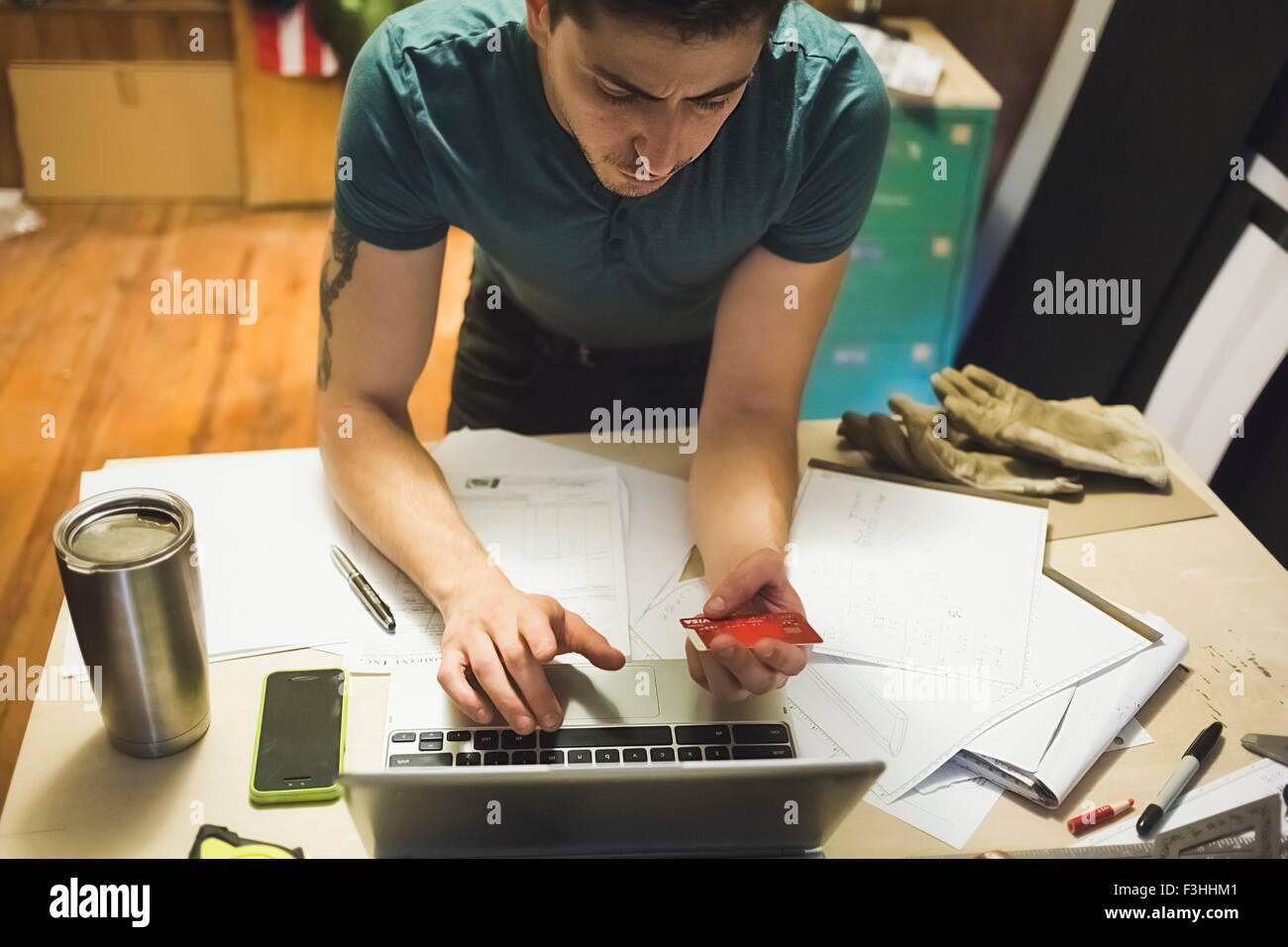 Portrait de jeune homme à l'aide de carte de crédit et d'ordinateur portable pour faire des achats Photo Stock