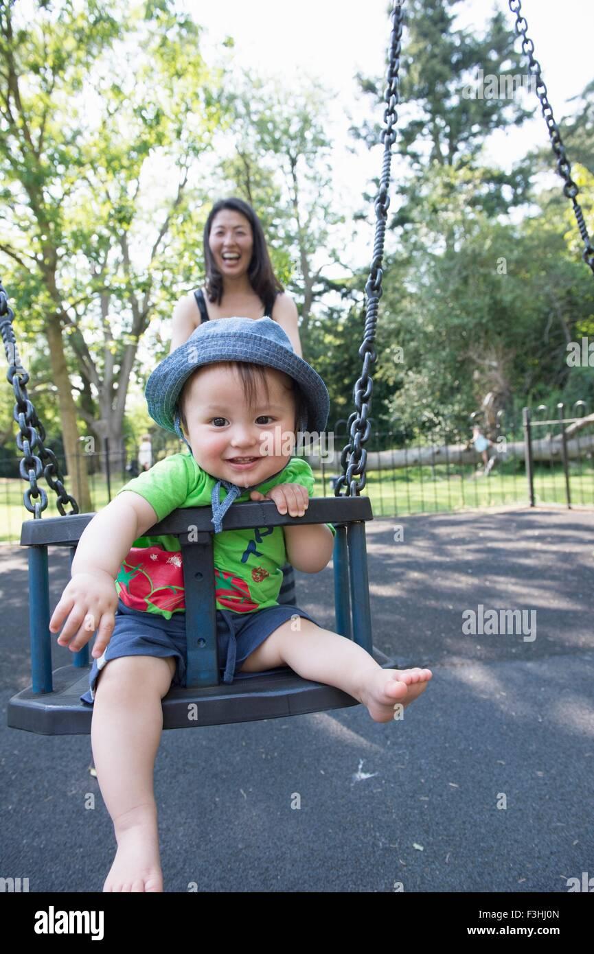 Portrait of baby boy avec mère jouant sur swing park Photo Stock